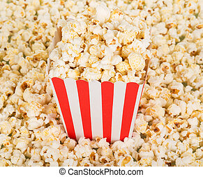 Large square box of popcorn and lot popcorn around....