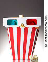 Large square box popcorn and 3D glasses, several beside...