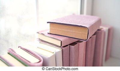 Large stack of books on windowsill. Books wrapped in colored...