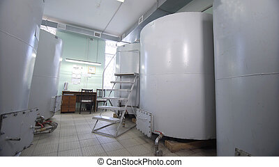 Large stainless steel alcoholic beverages distilling tanks. Silos for wine and cognac fermentation in distillery. On tanks written: number and volume of tanks