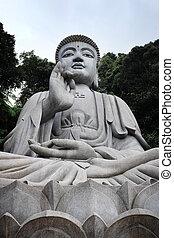 Large stone Buddha statue surrounded by rainforest