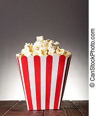 Large striped square box filled with popcorn on gray...