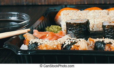 Large sushi set with a variety of sushi rolls as well as maki, nigiri, gunkan on a stylish black wooden background