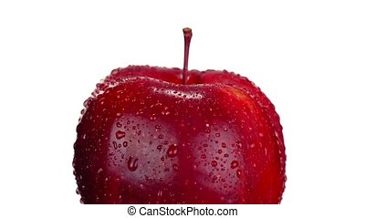Large sweet red apple with small stem covered with shiny clear water drops turns left side on white background extreme closeup