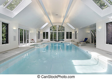 Large swimming pool in luxury home with skylights