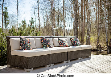 Large terrace patio with rattan garden furniture set. Wooden garden lounge chair with cushion. comfortable rattan sofa. relaxing area outside .patio with furniture on wooden floor. relaxation on the terrace
