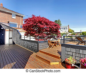 Large terrace with furniture in the front of the house.