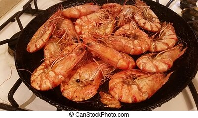 Large tiger shrimps are fried in a frying pan