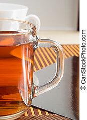 Large transparent glass mug with tea close up
