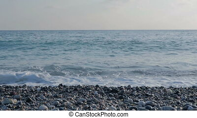 Large transparent waves with foam. Sea pebble beach with colorful stones.