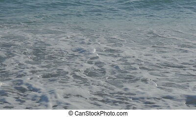 Large transparent waves with foam. Sea pebble beach with colorful stones