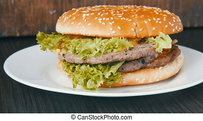 Large triple burger with lettuce leaves on a white plate....