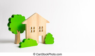 Large two-story house surrounded by bushes and trees. Urbanism and urban landscaping. Acquisition of affordable housing in a mortgage. Accommodation for young families. Apartments for rent