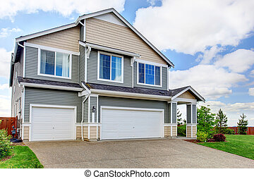 Large two story house with siding, two garage spaces and concrete driveway