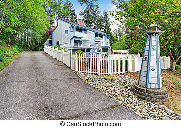 Large two story marine style home with long concrete driveway.