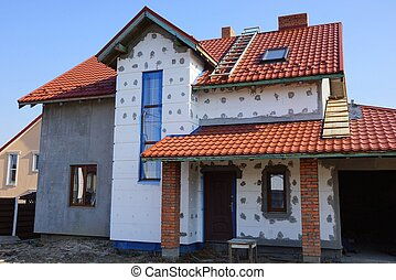 large unfinished private house with white insulation on a gray wall under a red tile roof