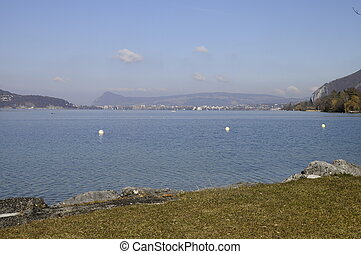 Large view of Annecy lake and city with grass beach in foreground