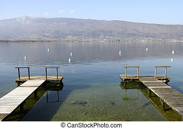 Large view of Annecy lake and mountains from two wooden pontoons, France
