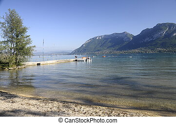 Large view of Annecy lake and mountains with rowing boats from Saint-Jorioz beach, France
