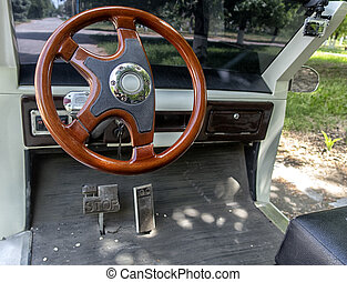 Large view of the steering wheel and electric car pedals.