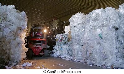Large warehouse of waste paper in a factory. - Loader sorts...