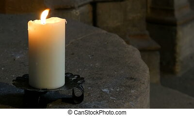 Large wax white candle burns and stands in an old...