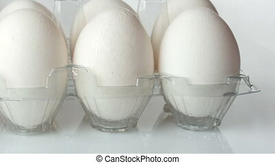 Large white chicken eggs in transparent plastic tray on a...