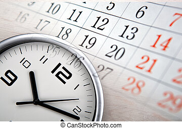 large white clock face with calendar sheets