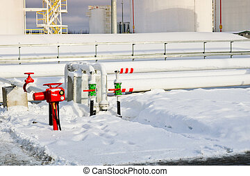Large white iron metal industrial tanks for storage of fuel, gasoline and diesel and pipeline with valves and flanges at the refinery in the winter
