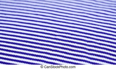 white piece of cloth with blue stripes lies and rotates