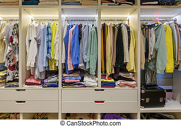 Large woman's wardrobe with different clothes, front view