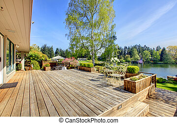 Large wood deck near house with lake and spring landscape.