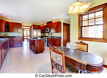 Large wood kitchen with dining room table.