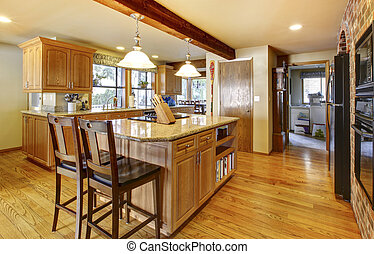 Large wood kitchen with hardwod floor and wood beam.
