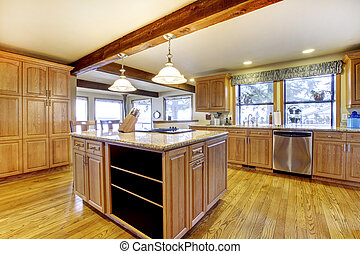 Large wood kitchen with island and wood beam.