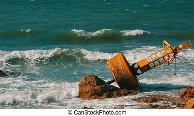 Large yellow buoy on the shores of azure sea. The waves hit the buoy and the big rocks on the shore