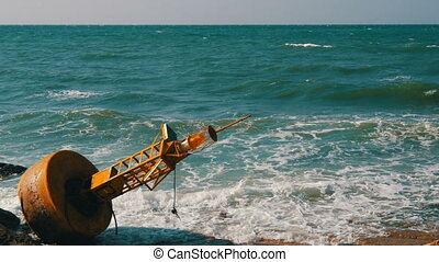Large yellow buoy on the shores of azure sea. The waves hit...
