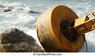 Large yellow buoy on the shores of azure sea. Waves hit the...