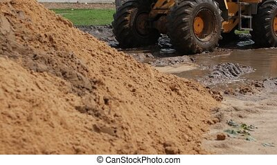 Large yellow forklift construction machinery riding mud, slow mo