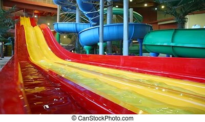 Large yellow plastic slide is filled a water in a large...