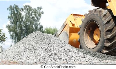 Large yellow tractor loader collects small gravel in the...