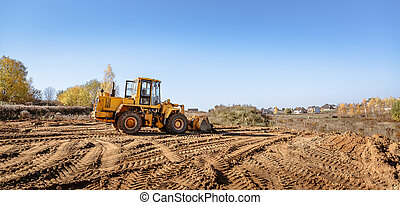 large yellow wheel loader aligns a piece of land for a new building. Preparation of the land for the auction. Leveling the landscape and adding sand for construction. Banner wallpaper