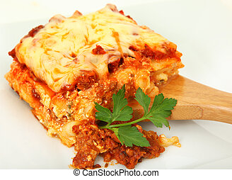 Square of baked lasagna with parsley on bamboo serving spoon