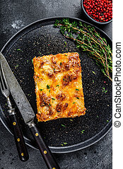 Lasagna with mince beef meat and tomato bolognese sauce on a plate. Black background. Top view