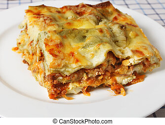 A slice of lasagne verde (spinach lasagna) on a plate, seen closeup