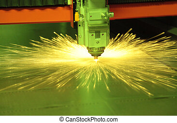Laser cutting metal sheet in factory, with sparks flying...