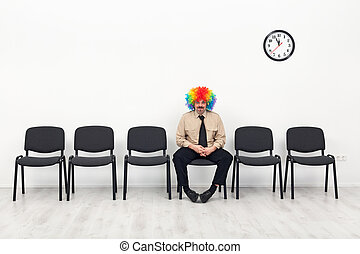 Last man standing - waiting concept with clown in business...