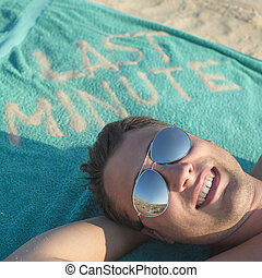 Guy enjoying last minute booking on tropical beach. travelling concept
