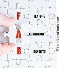 Last puzzle piece with Business Acronym FAB - Hand of a...