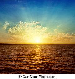 last sunrays in clouds over orange water